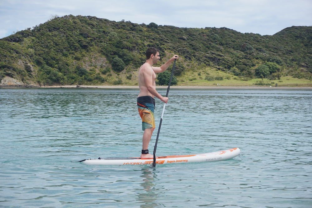 stand paddle boarding at the rock bay of islands